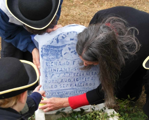 TP shows children learning to make a rubbing of a gravestone