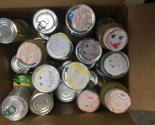 TP shows happy faces drawn by children, put on Food Pantry Cans