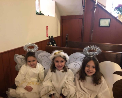 TP shows three children dressed as angels for the Christmas Pageant