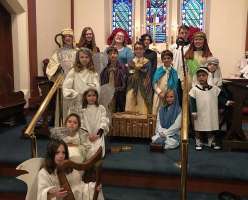 TP shows Christmas Pageant cast arrayed in front of altar