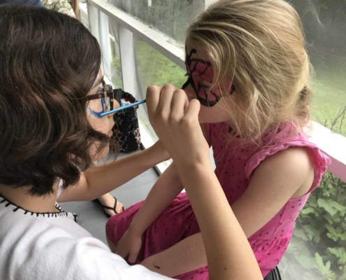 TP shows a Youth member painting a child's face at Parish Picnic