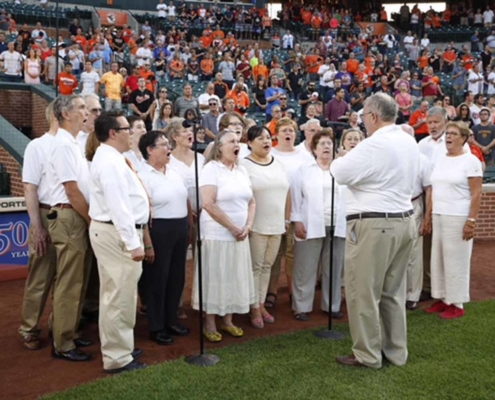 TP shows the choir singing the National Anthem at Orioles Park