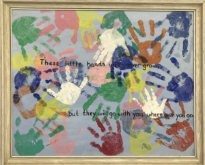 TP shows children sharing their handprints in one piece of art