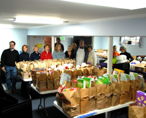 TP shows volunteers at a Food Pantry distribution with bags packed with food to give away