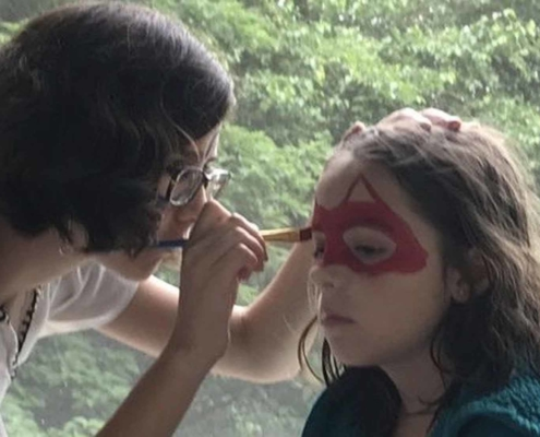 TP Youth member painting a child's face at a Parish Picnic