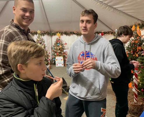 TP shows Youth Group members relaxing after decorating their Lights of Kindness tree